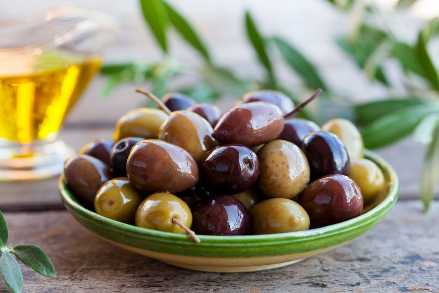 Assortment of fresh olives on a plate with olive tree brunches. Wooden background